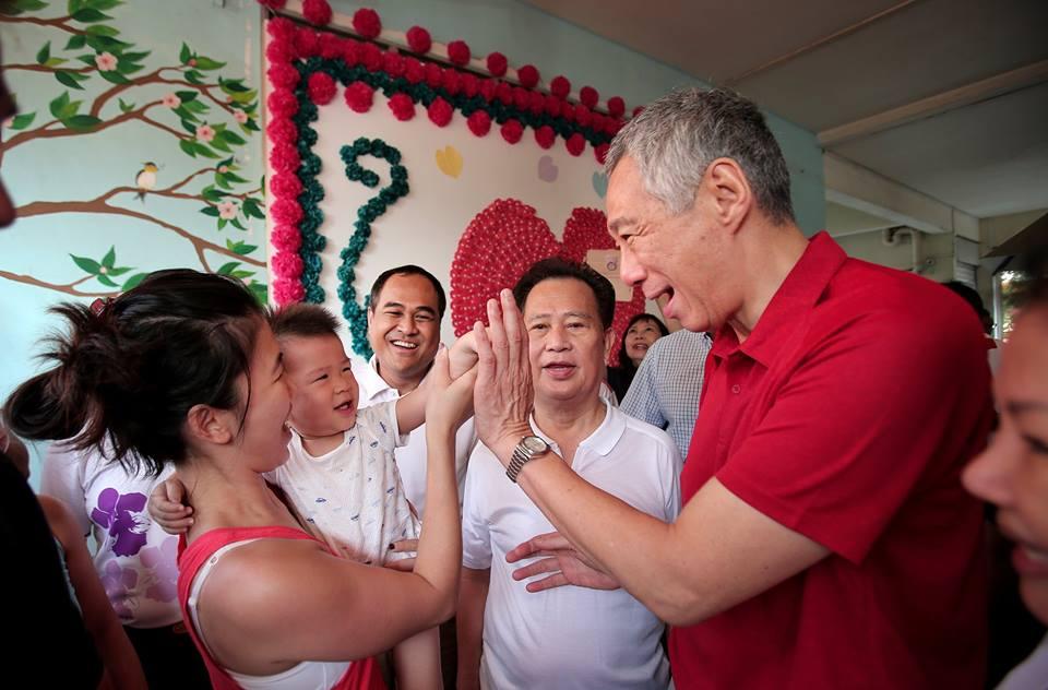 """Thủ tướng Singapore Lý Hiển Long tới thăm một trung tâm phúc lợi xã hội giữa tháng 3/2018 và """"high - five"""" với một em bé 17 tháng tuổi (Photo by Terence Tan)"""